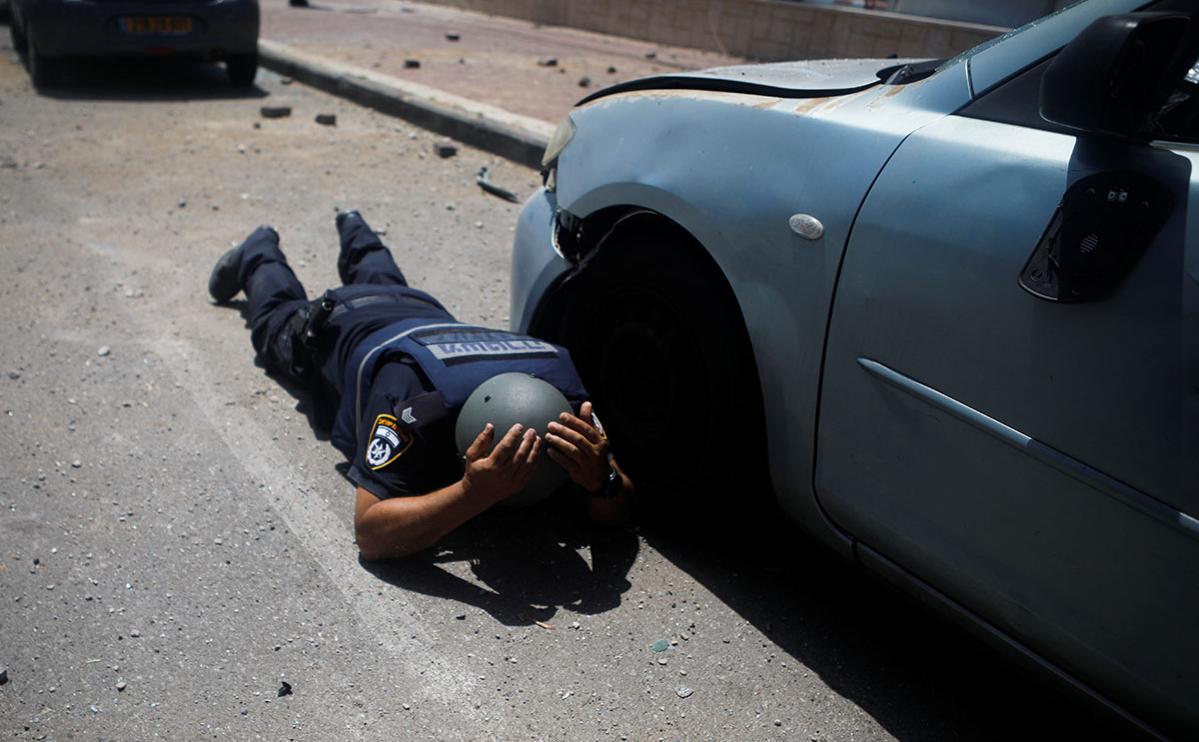 Израильский полицейский укрывается под звуками сирен, предупреждающих о приближающихся ракетах, запущенных из сектора Газа, в Ашкелоне, на юге Израиля, 11 мая 2021 года.