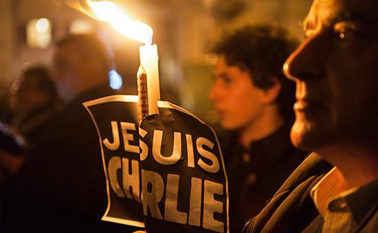 Человек держит свечу во время акции в знак солидарности с жертвами вчерашнего теракта в Париже
