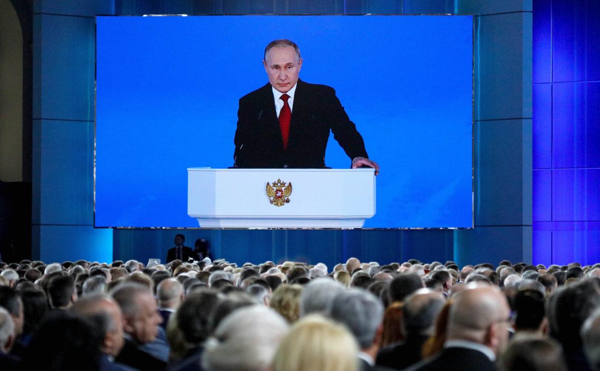 Владимир Путин (на экране) во время выступления с ежегодным посланием к Федеральному Собранию РФ