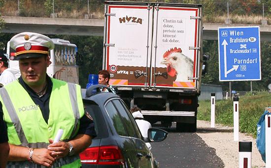 Сотрудник полиции на фоне грузовика, в котором были обнаружены тела погибших мигрантов