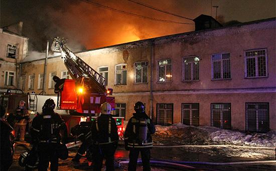 Сотрудники пожарной охраны у производственного здания швейного цеха на улице Стромынка, где произошел пожар