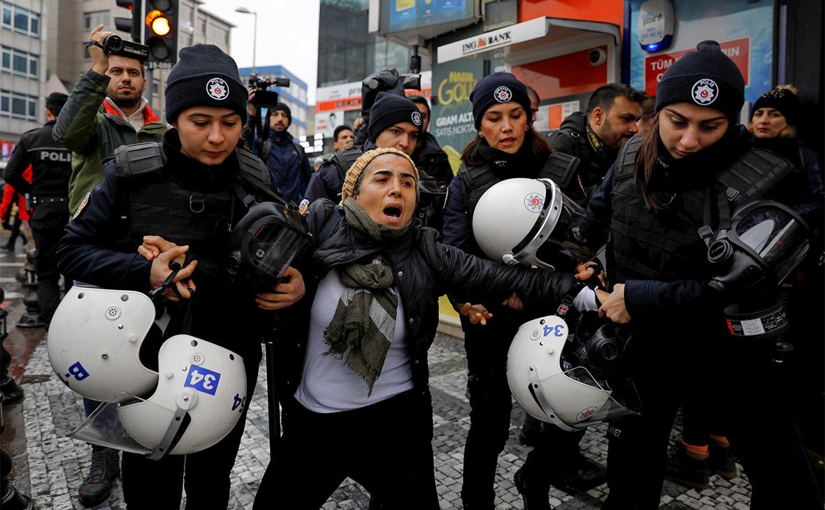 Сотрудники полиции задерживают демонстрантку на митинге в Стамбуле против военных действий Турции в Сирии