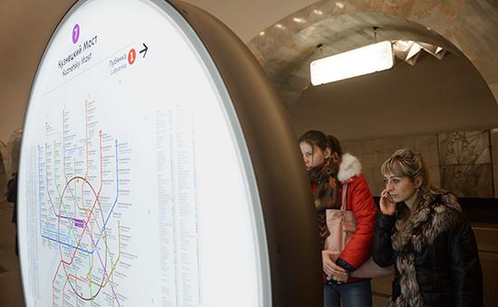 Пассажиры у информационного стенда на станции метро