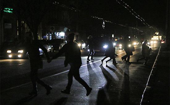Жители Симферополя переходят автодорогу в свете фар автомобилей. Крым, 22 ноября 2015 года