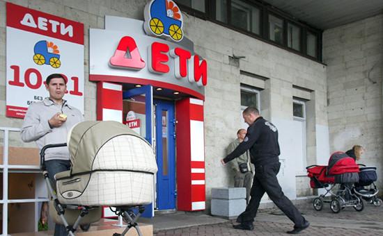 Мужчина сколяской стоит передвходом вмагазин «Дети». Санкт-Петербург, 2009 год