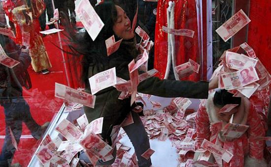 Женщина пытается поймать банкноту в сто юанейна аттракционе в преддверии праздника весны. Ханчжоу, Китай