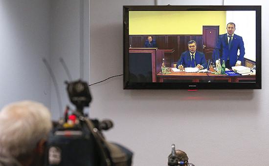 Бывший президент Украины Виктор Янукович иадвокат Виталий Сердюк (на мониторе слева направо), находящиеся вРостовском областном суде, врежиме видеоконференции дает показания