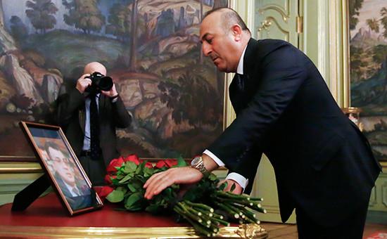 Министр иностранных дел Турции Мевлют Чавушоглу во время возложения цветов к портрету убитого накануне российского посла в Турции Андрея Карлова