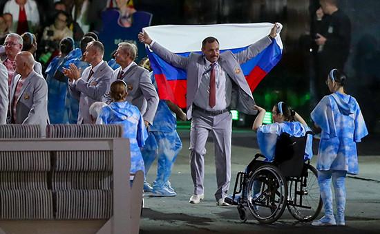 Член белорусской делегации Андрей Фомочкин несет флаг России нацеремонии открытия XV Паралимпийских летнихигр, 7 сентября 2016 года