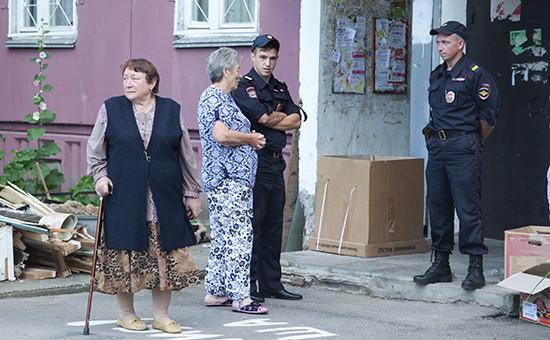 Сотрудники правоохранительных органов у подъезда жилого дома, где проживала многодетная семья с шестью детьми