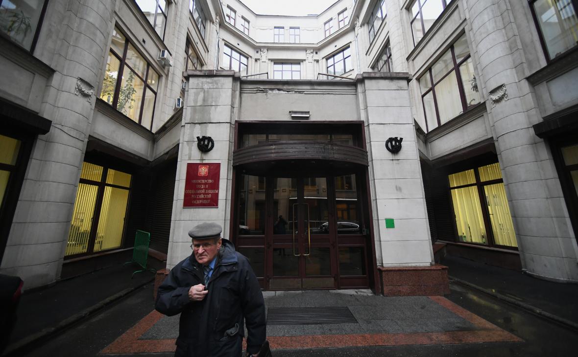Мужчина выходит из здания Министерства труда и социальной защиты Российской Федерации в Москве
