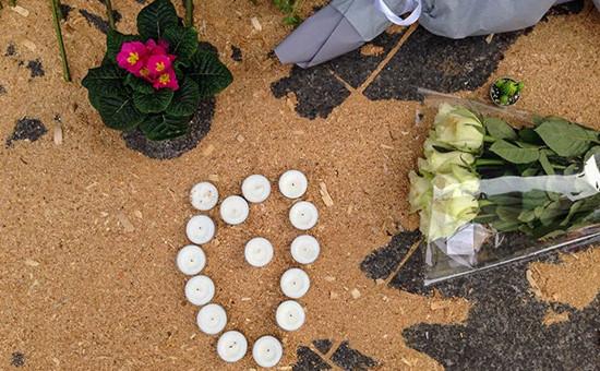 Принесенные парижанами цветы и свечи на месте убийства
