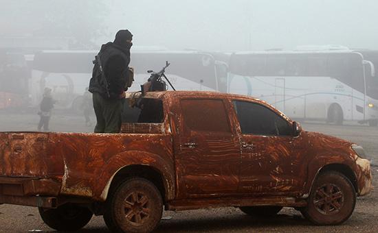 Боец вооруженной оппозиции у автобусов дляэвакуации мирных жителей иззоны соприкосновения справительственными войсками Сирии. Апрель 2017 года