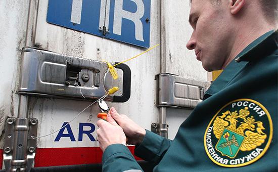 Работник таможенного поста российско-польской границы снимает пломбу сприбывшей натерминал фуры длядальнейшего досмотра