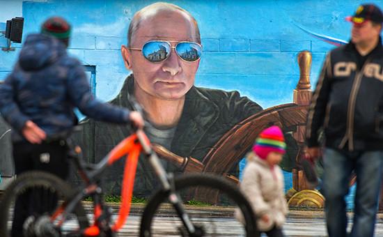 Прохожие у портрета президента России Владимира Путина на стене здания