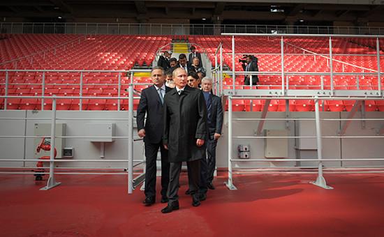 Президент России Владимир Путин (в центре) и министр спорта РФ Виталий Мутко (слева)вовремя посещения стадиона «Открытие Арена». Архивное фото