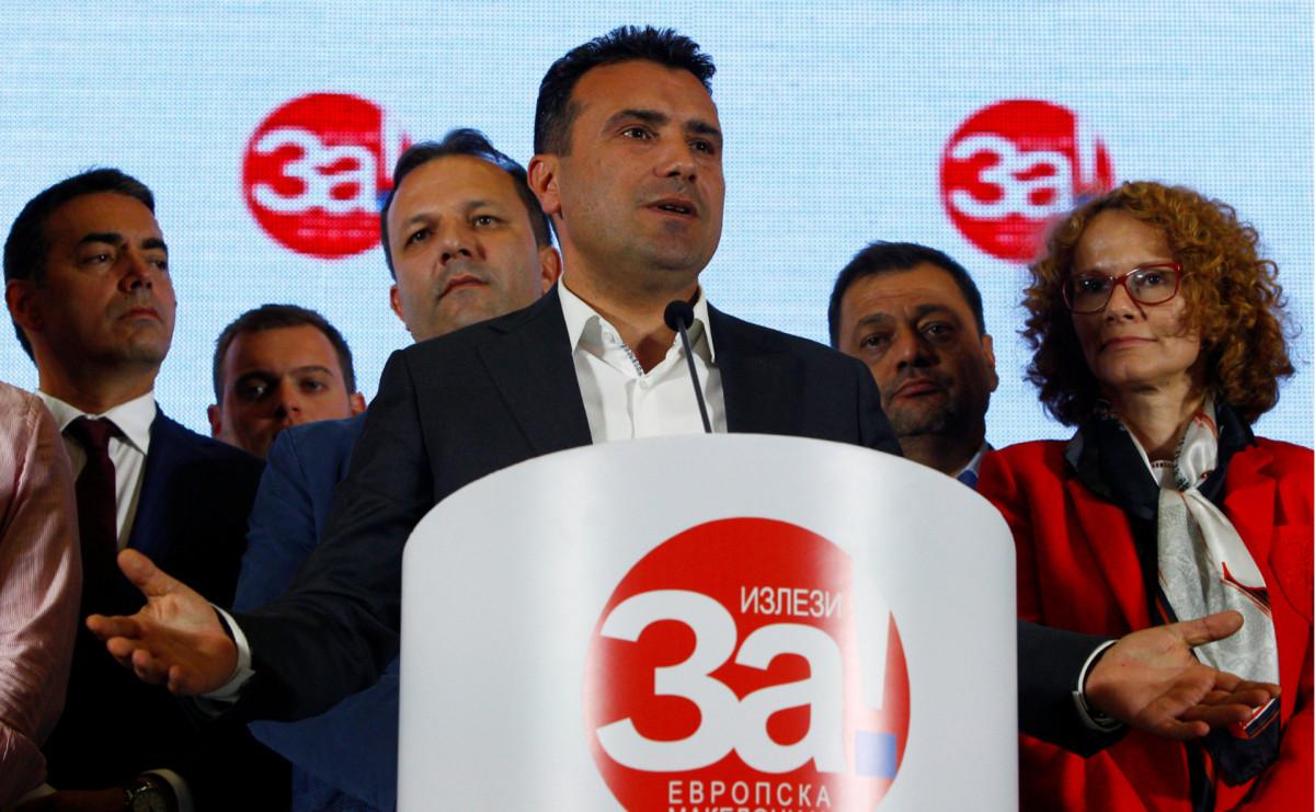 Премьер Македонии Зоран Заев стоит за трибуной с логотипом «Европейская Македония»