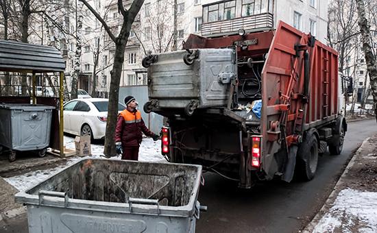 Сотрудник коммунальных служб выгружает мусор из контейнера в мусоровоз.
