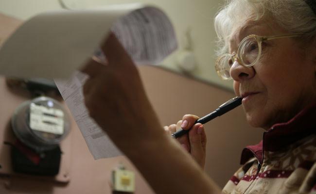 Женщина заполняет квитанции на оплату коммунальных услуг