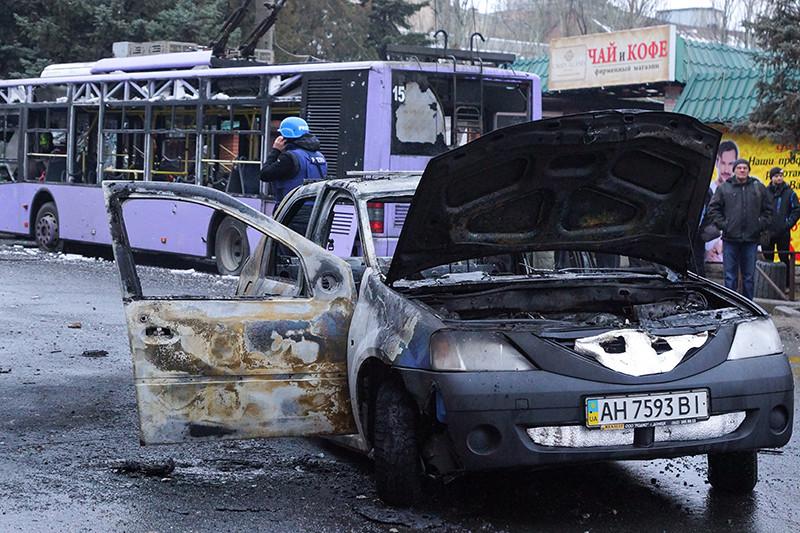 Сгоревший автомобиль на месте обстрела остановки общественного транспорта в Ленинском районе Донецка