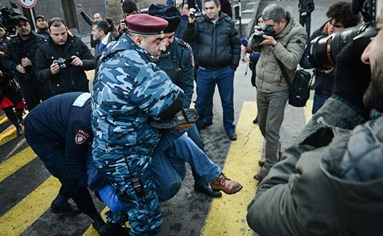 Сотрудники службы безопасности несут мужчину во время акции протеста у посольства России в Ереване