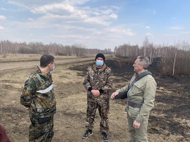 Губернатор (справа) инспектирует территории, где горят леса и поля.