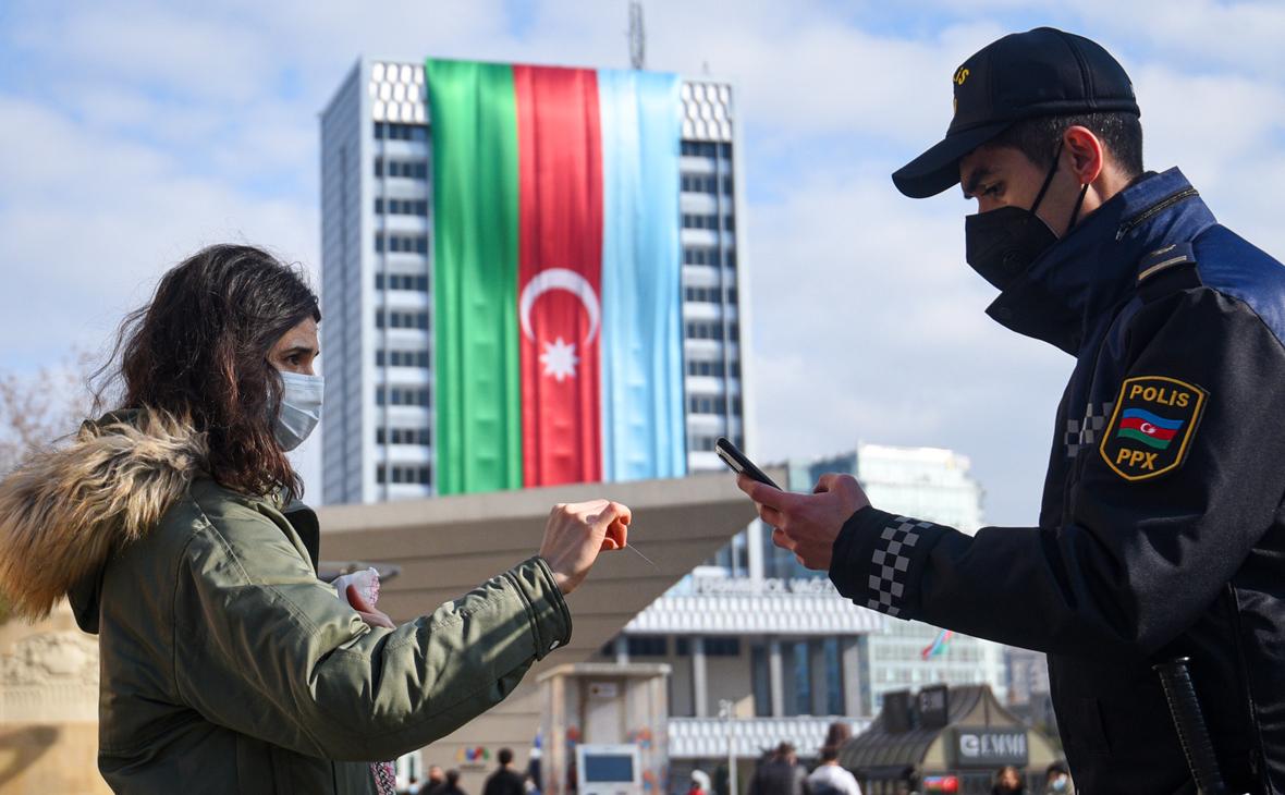 Сотрудник полиции проверяет пропуск у девушки на одной из улиц в Баку