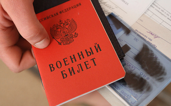 Новобранец держит документы во время оформления на сборном призывном пункте