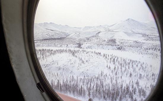 Вид изиллюминатора самолета наземлю Якутии
