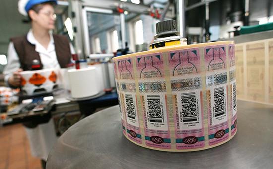 Сотрудники ликероводочного завода работают на линии розлива подакцизной алкогольной продукции