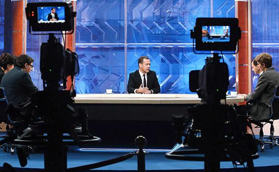 Премьер-министр России Дмитрий Медведев (в центре) вовремя интервью, посвященного итогам работы правительства втекущем году, журналистам пяти российских телеканалов встудии телецентра «Останкино»