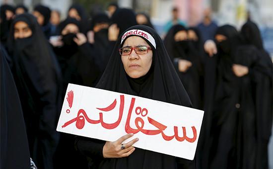 Мусульманка держит плакат «В ад вместе стобой» вовремя демонстрации противказни проповедника Нимра аль-Нимра. 2 января 2016 года, Бахрейн