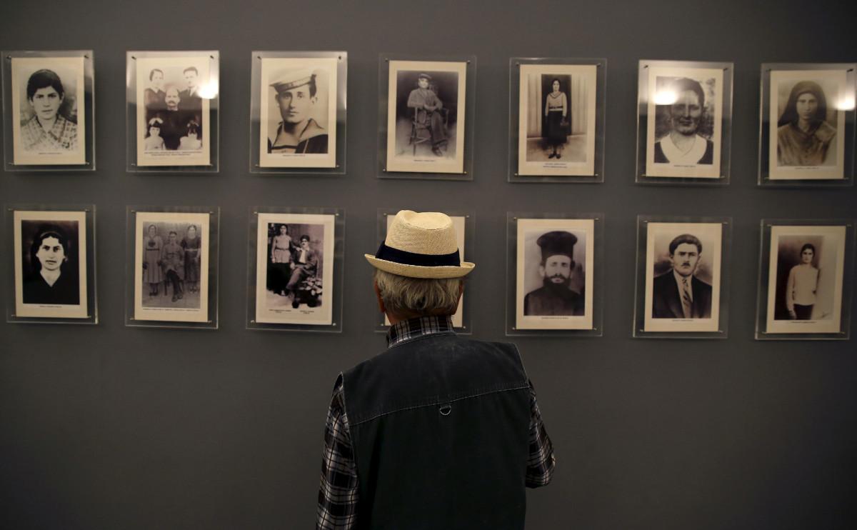 Родственник жертв нацистской оккупации смотрит на мемориальную стену с фотографиями погибших
