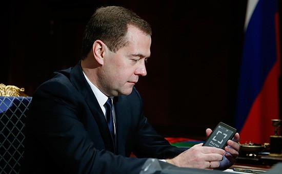 Председатель правительства РФ Дмитрий Медведев рассматриваетсмартфон сжидкокристаллическим экраном, продемонстрированныйгенеральным директором Государственной корпорации «Ростехнологии» СергеемЧемезовым, 2013 год