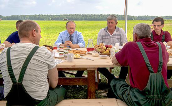 Президент России Владимир Путин (слева навтором плане) общается смеханизаторами, 28 июля 2016 года