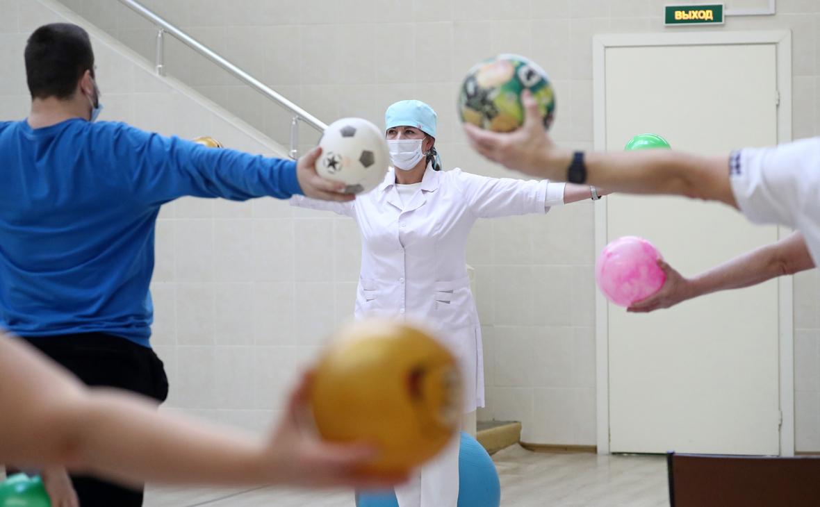 Медицинский работник и пациенты, ранее переболевшие коронавирусом, во время занятия лечебной физической культурой в рамках программы по реабилитации