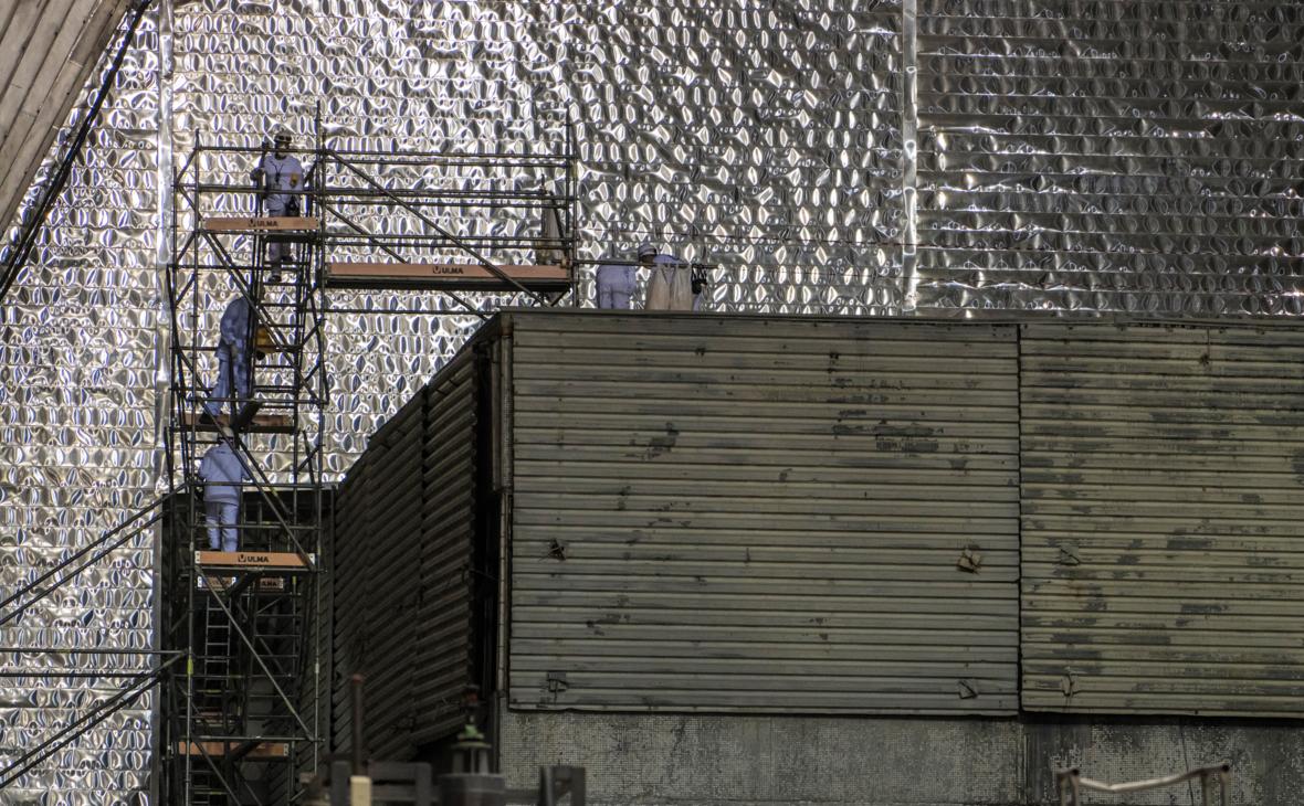 Рабочие около разрушенного в результате аварии 4-ого энергоблока Чернобыльской АЭС под изоляционным арочным сооружением