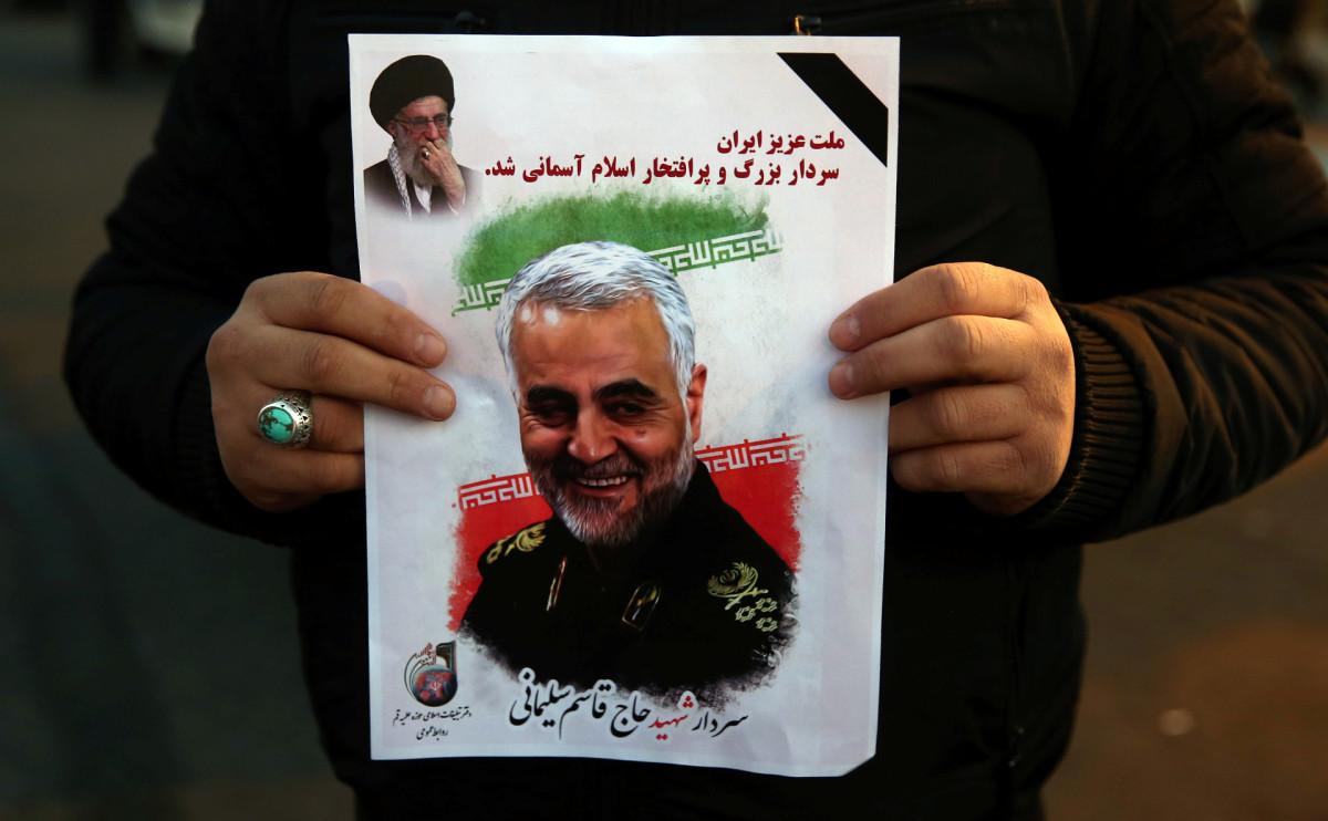 Мужчина держит фотографию убитого США генерал-майора Ирана Касема Сулеймани