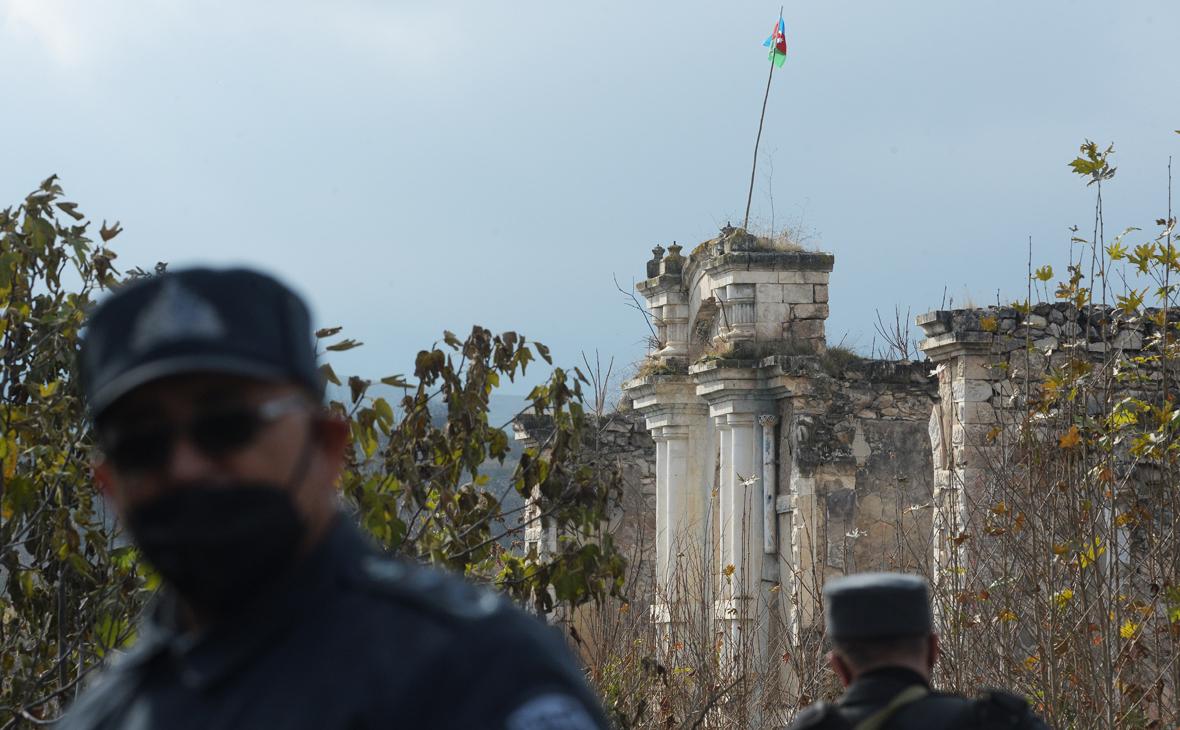 Азербайджанские полицейские у разрушенного здания в городе Физули