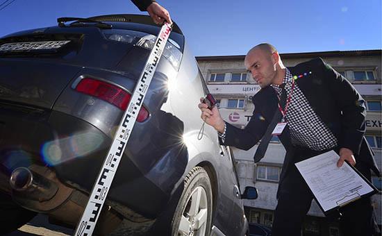 Сотрудник страховой компании «Росгосстрах» фиксирует повреждения автомобиля, попавшего в ДТП. Архивное фото