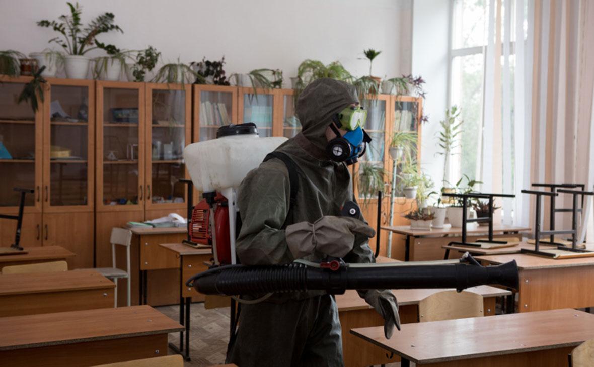 Работник МЧС России обрабатывает школуперед ЕГЭ