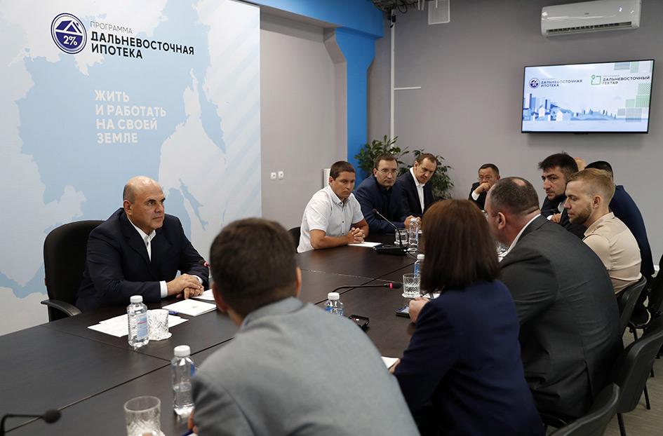 Премьер-министр России Михаил Мишустин (слева на втором плане) во время встречи в Благовещенске по государственным программам «Дальневосточный гектар» и «Дальневосточная ипотека»