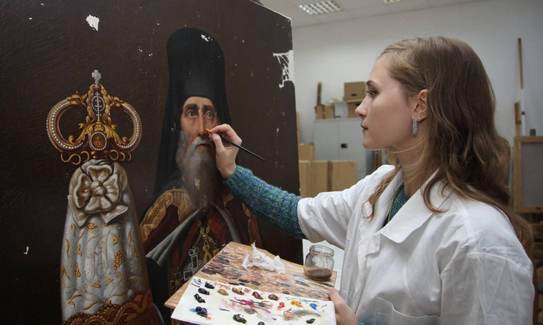 Инга Федорова в процессе реставрации картины «Портрет священнослужителя»