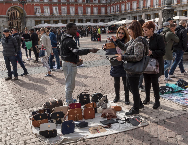 Туристы разглядывают поддельные сумки Tous и Michael Kors