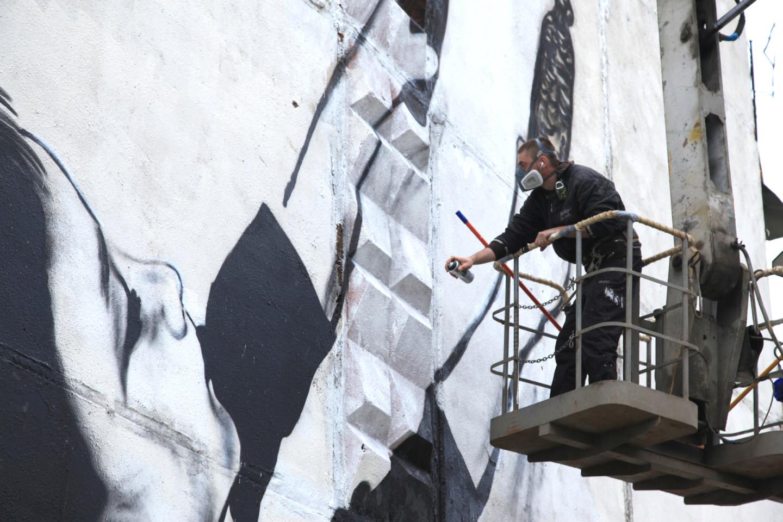 Паша 183 во время работы над муралом «Сказка о потерянном времени»