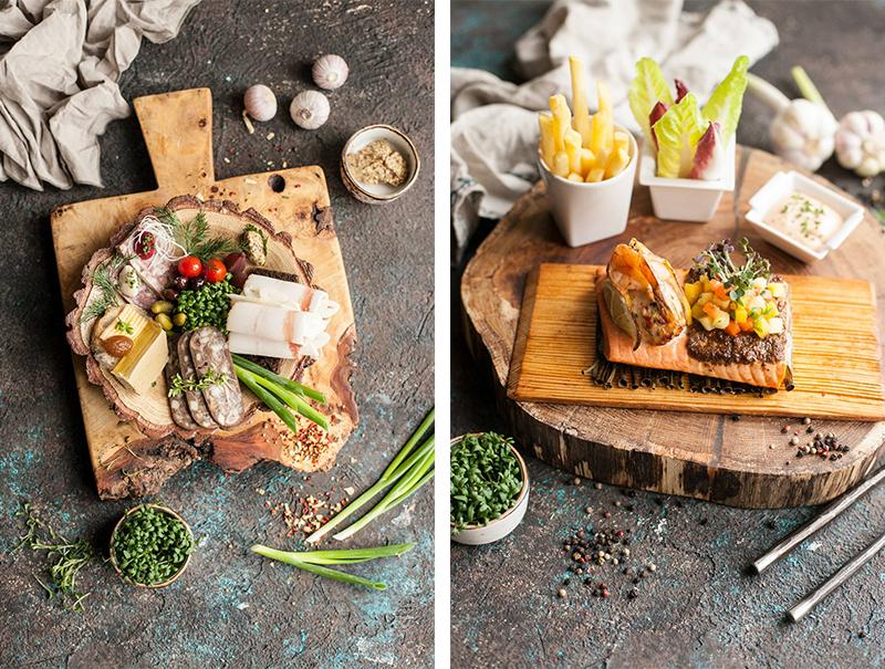 Закуска «Мясные припасы» на тарелке из мореного дуба. Дикий арктический лосось, подкопченный на ольховой дранке.