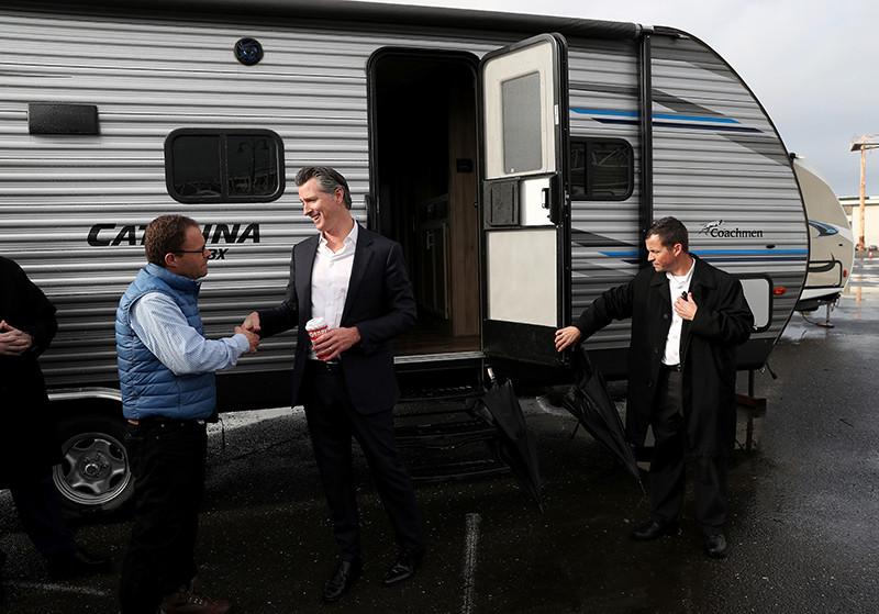 Гэвин Ньюсон приветствует людей у трейлеров FEMA после конференции, посвященной бездомным, Окленд, Калифорния