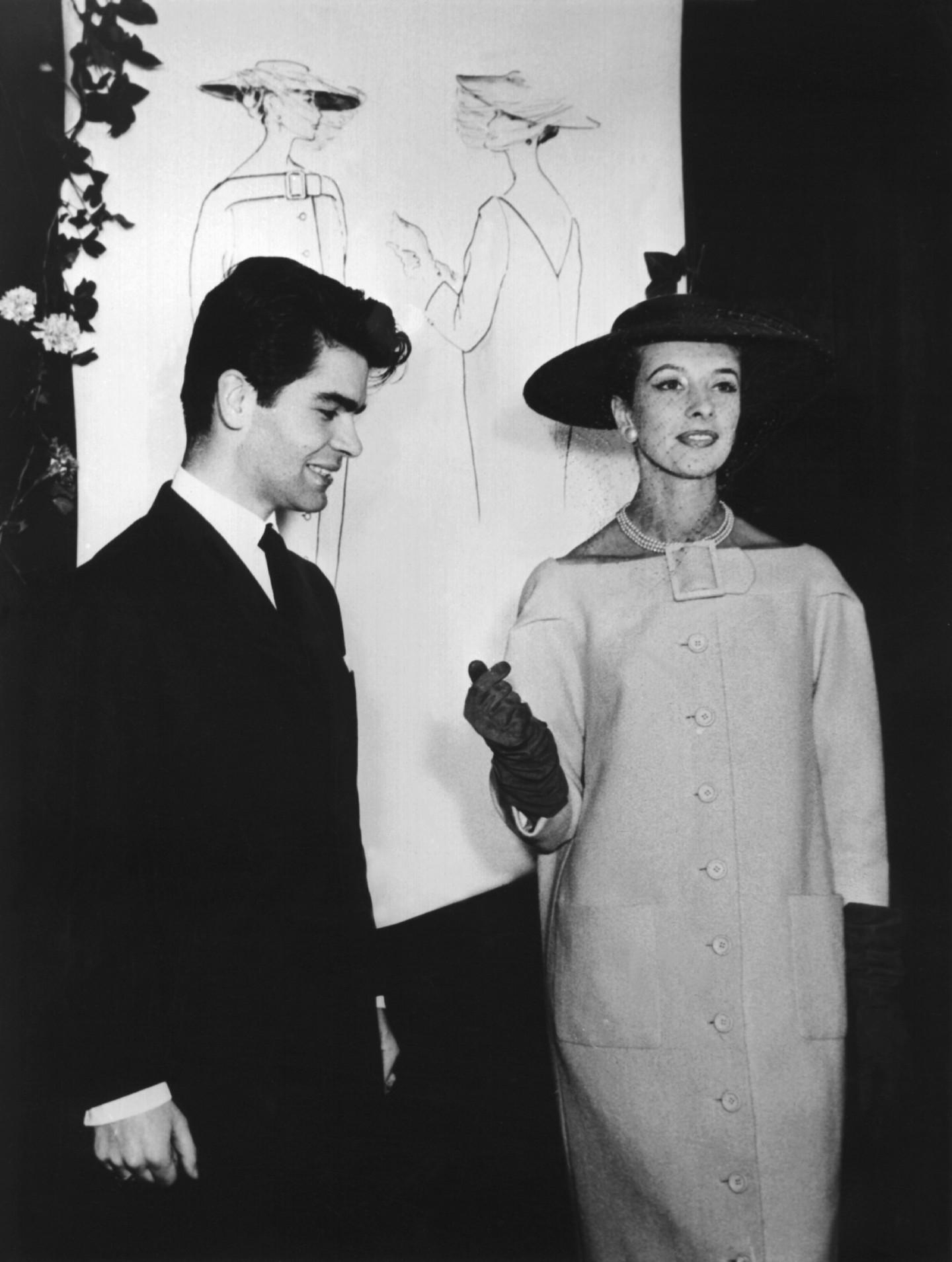 16-летний студент-дизайнер смоделью, демонстрирующей его пальто.Именно за него ЛагерфельдбылудостоенГран-при в1954 году