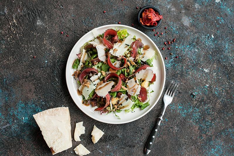 Салат с маринованной телятиной, пармезаном, вялеными томатами, печеными баклажанами, картофелем и чипсами из лука