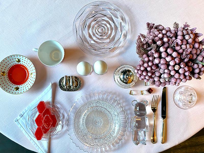 Набор из двух чашек с блюдцами Delphos & Knossos, Bernardaud; тарелки из коллекций Mille Nuits, Arabesque, Swing, стакан для воды Harmonie,скульптура медведя Baccarat x Be@rbrick, игральные кубики Baccarat x Marcel Wanders — все Baccarat; нож и вилка Perles, солонка и перечница Jardin d'Eden, масленка Albi — всеChristofle